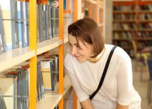 Nainen etsii kirjaa kirjastossa
